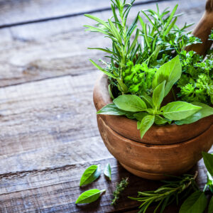 Image of herbs in a wooden bowl.