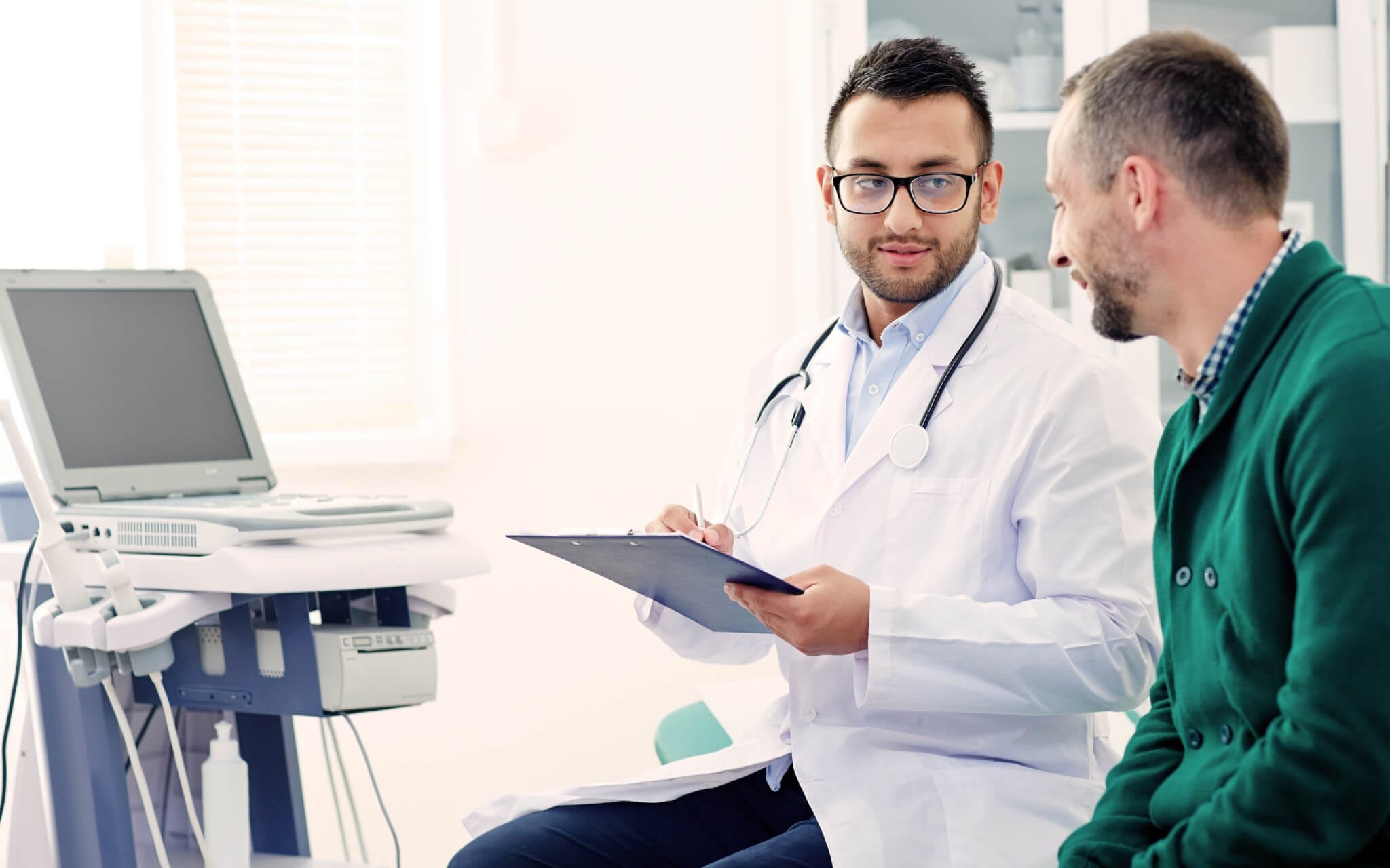A doctor goes over his patient's mesothelioma medical records and timeline on his clipboard as his patient looks on.