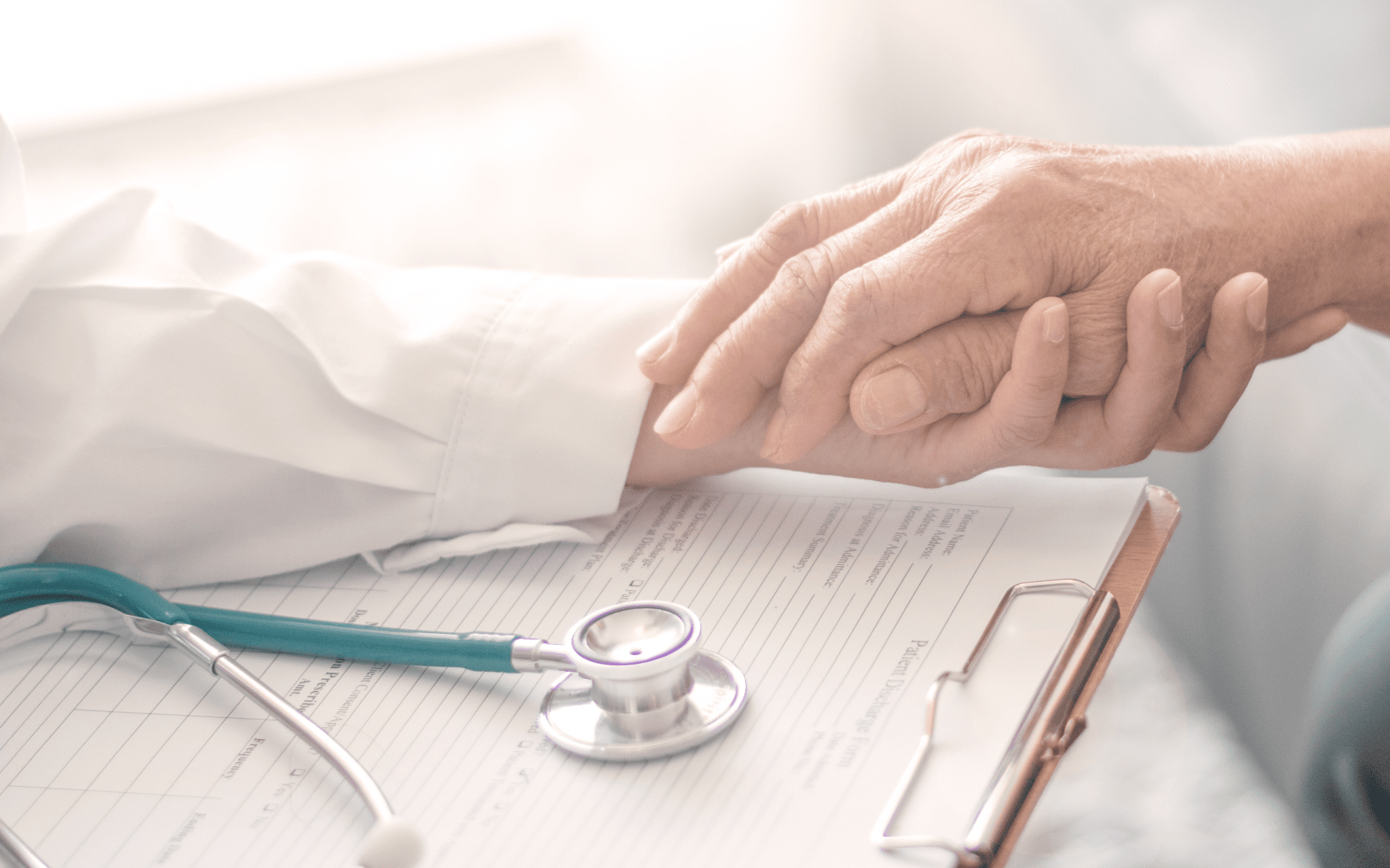 Closeup of a doctor holding their elderly patient's hand.