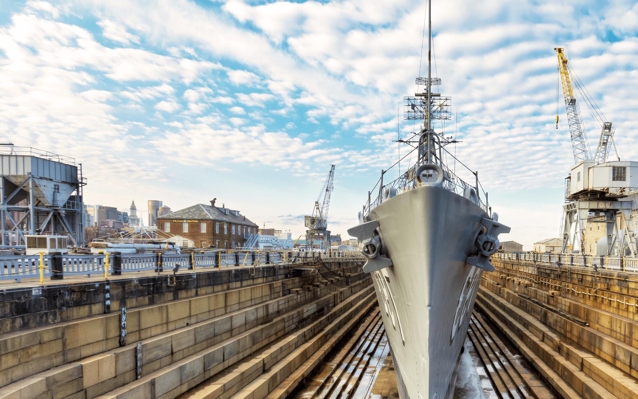 Naval ship sits in a boatyard.