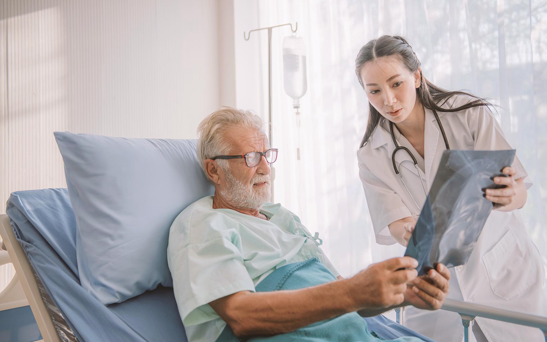 Doctor showing her bedridden patient an x-ray.