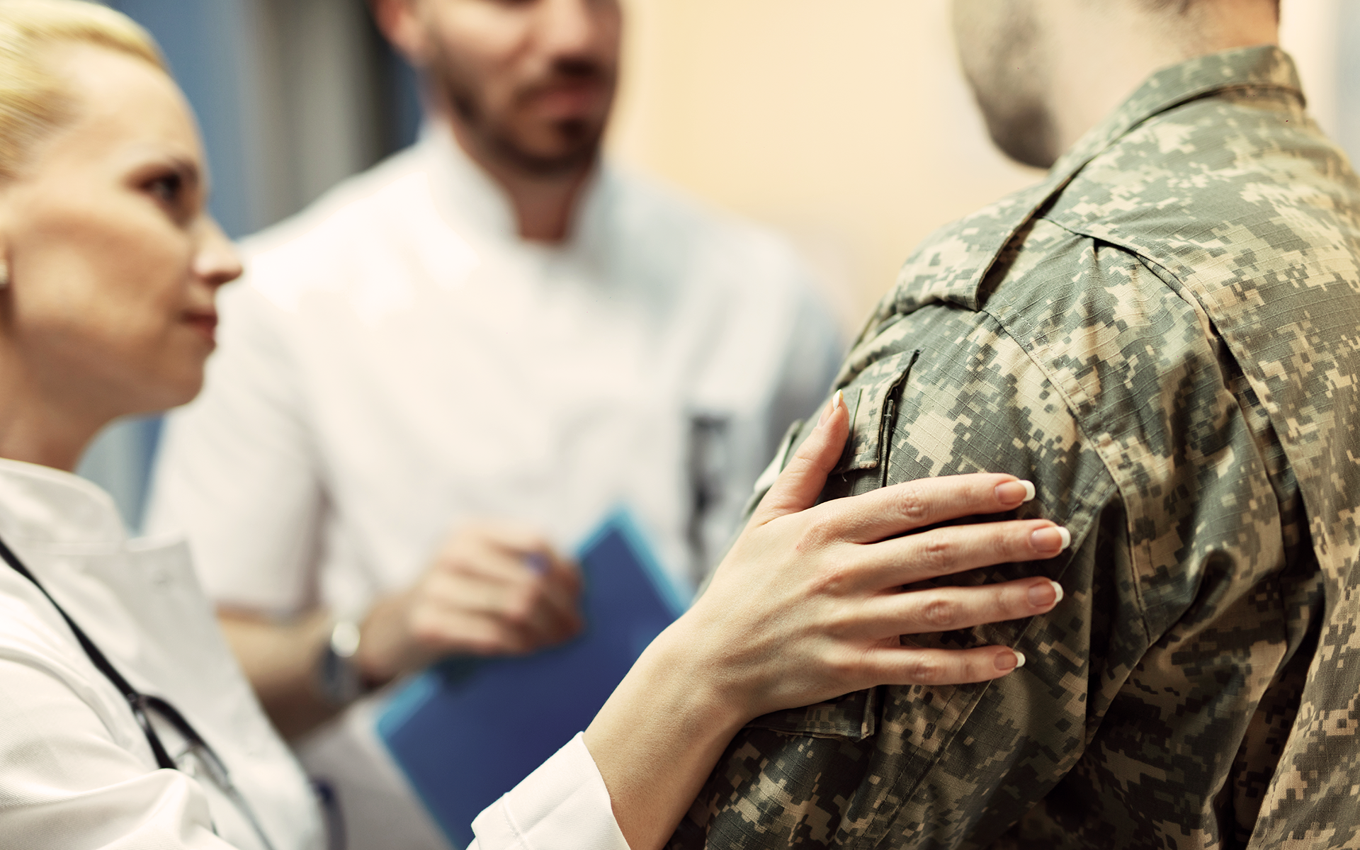 Doctor consoles veteran while they talk to another doctor.