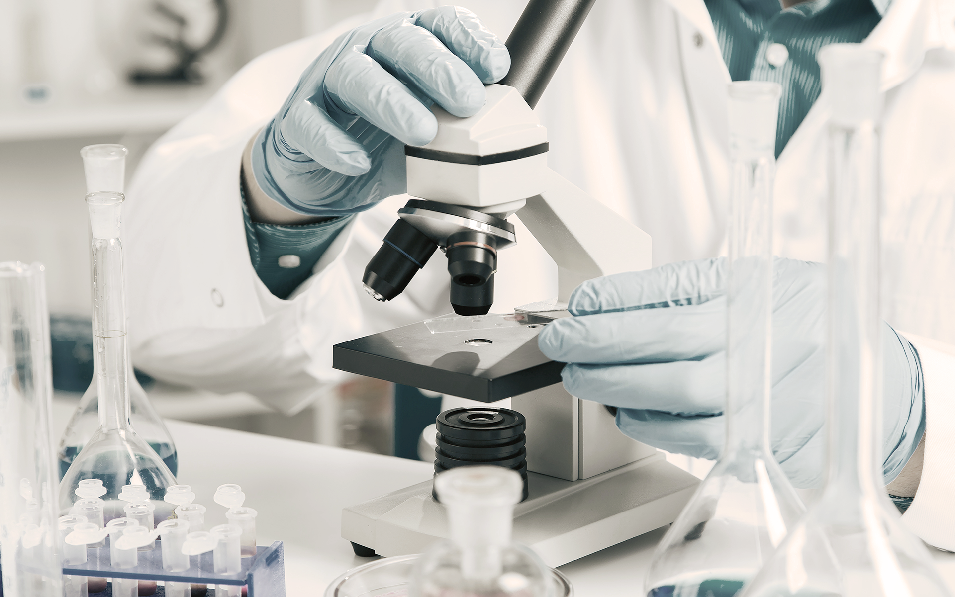 A doctor studying a sample under a microscope from a biopsy.