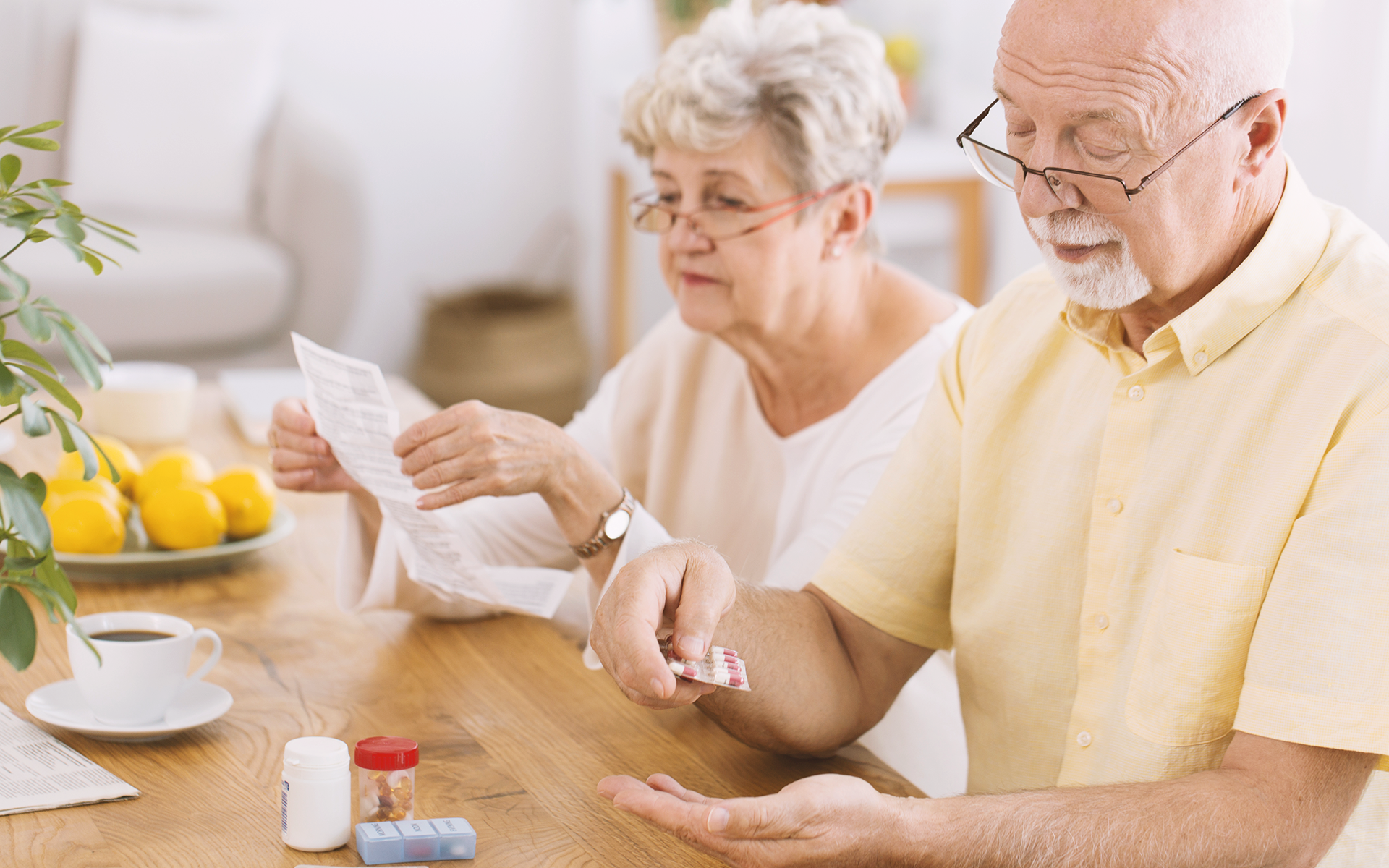 An elderly couple sorting through medications.