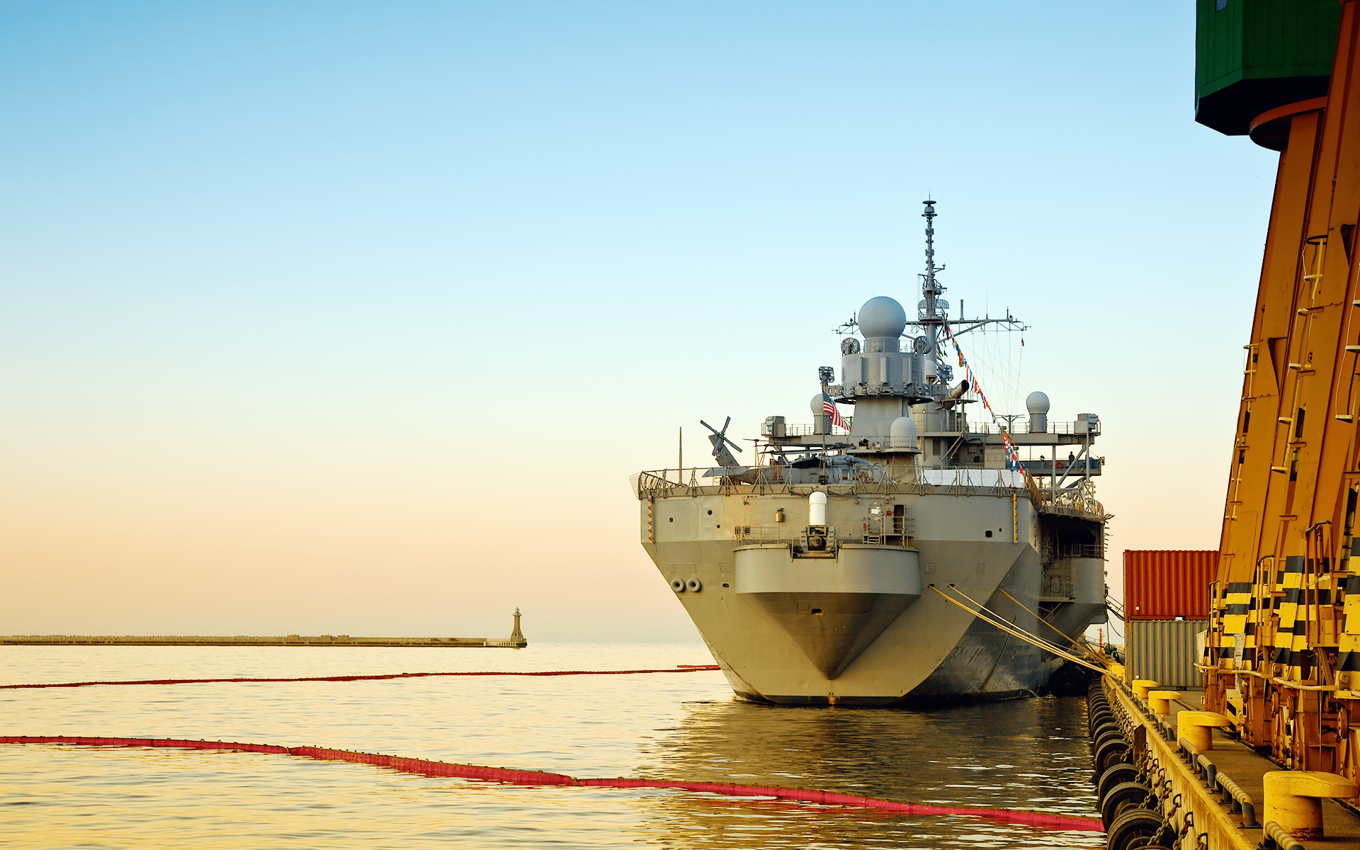 A Navy ship on the water in a harbor.