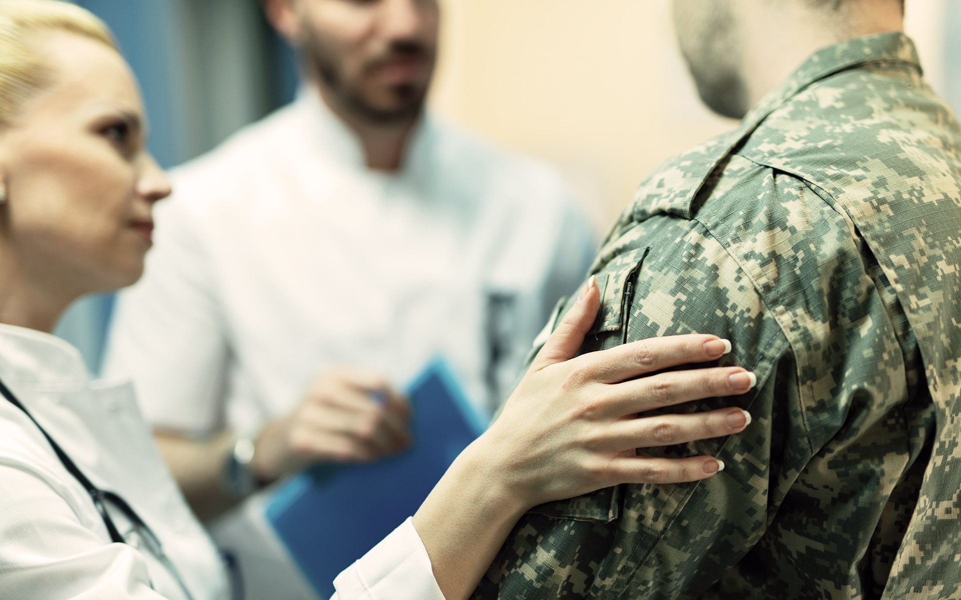 A female doctors pats the shoulder of a veteran while another doctor looks on.
