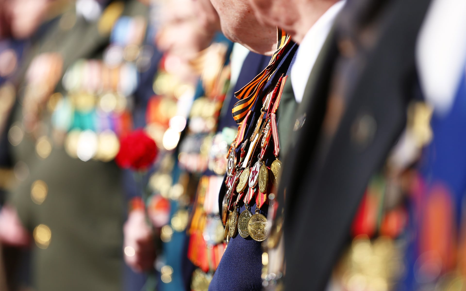 Closeup of military medals on the neck of a veteran at an award ceremony.