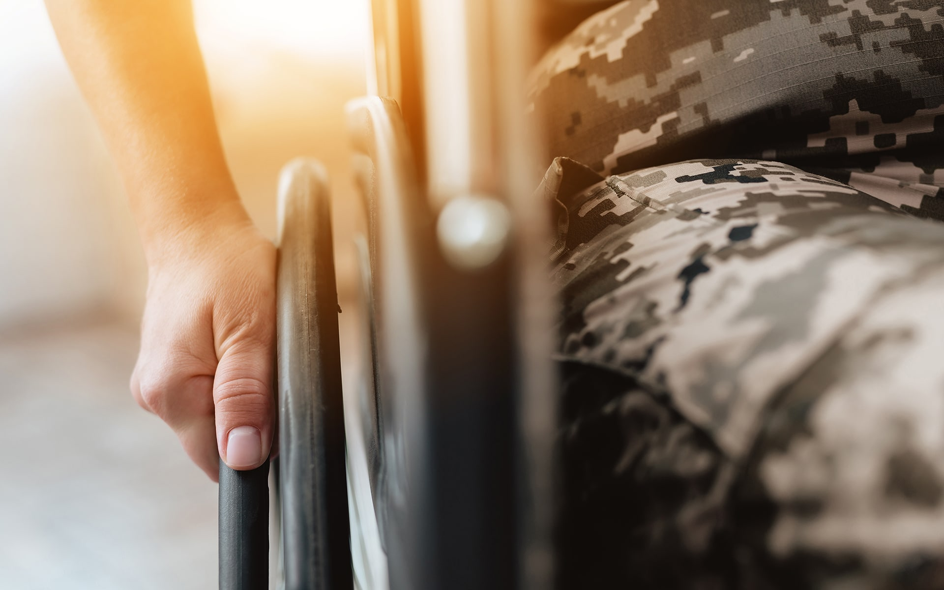 Closeup of a veteran's hand gripping the wheel on the side of their wheelchair.