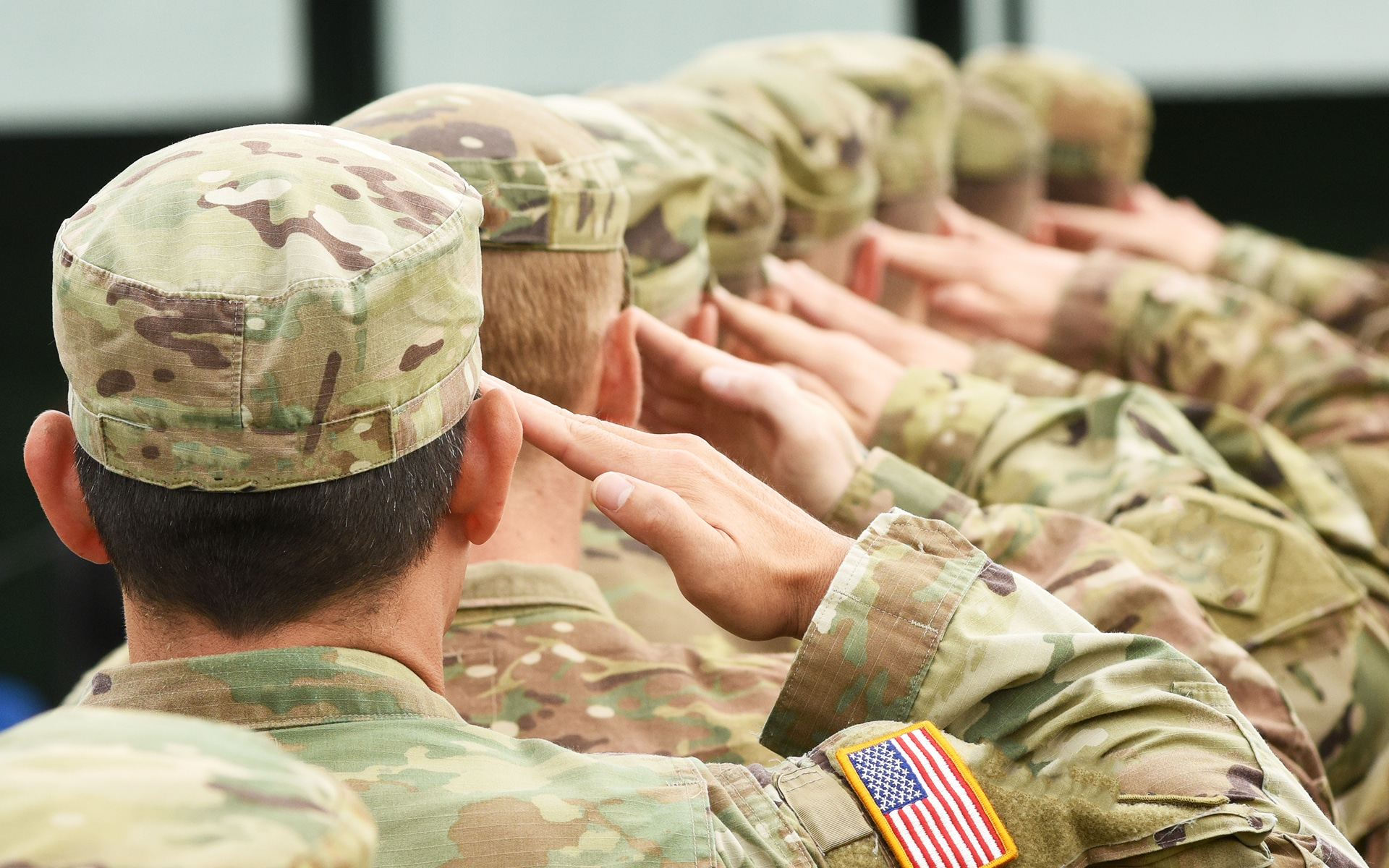 A line of veterans saluting forward in a straight line.