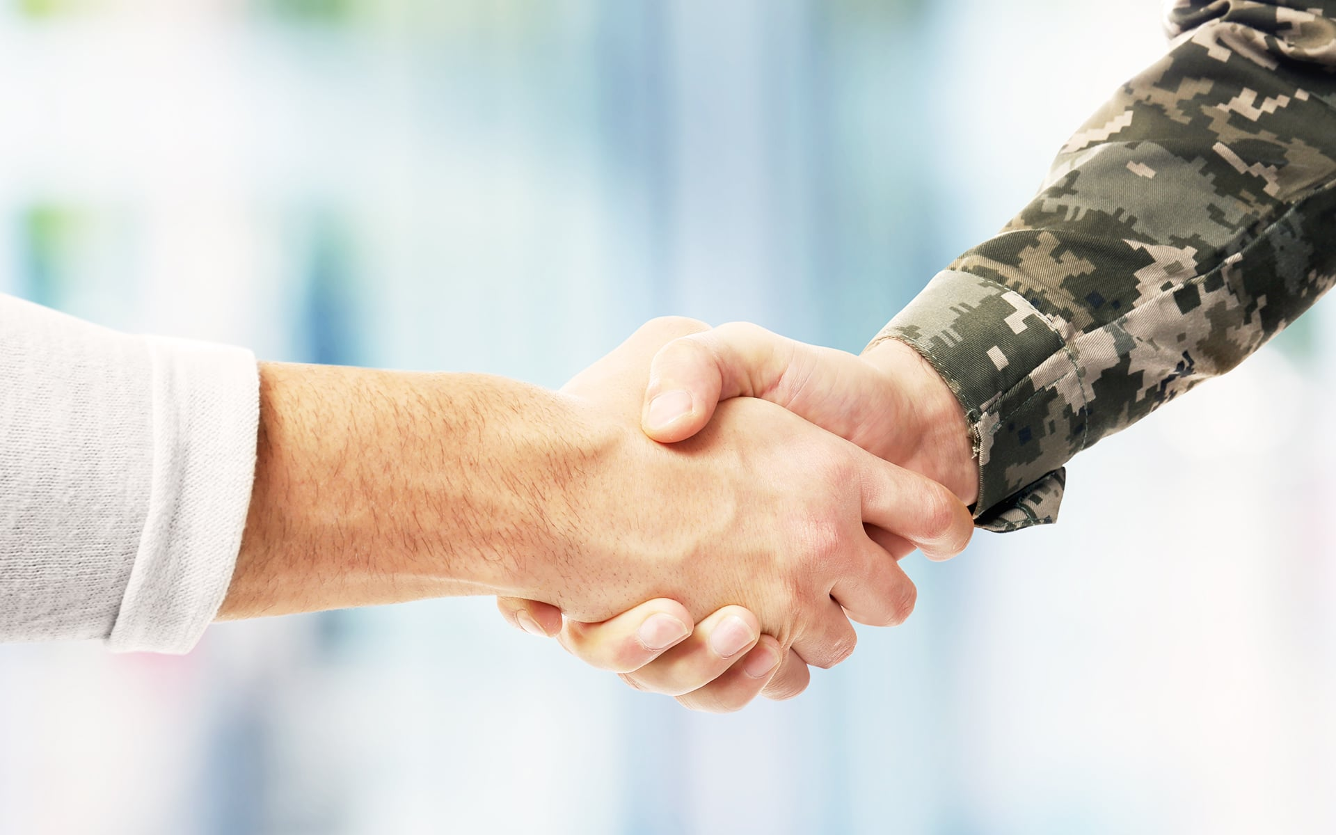 Closeup of two shaking hands, one belonging to a Veteran.
