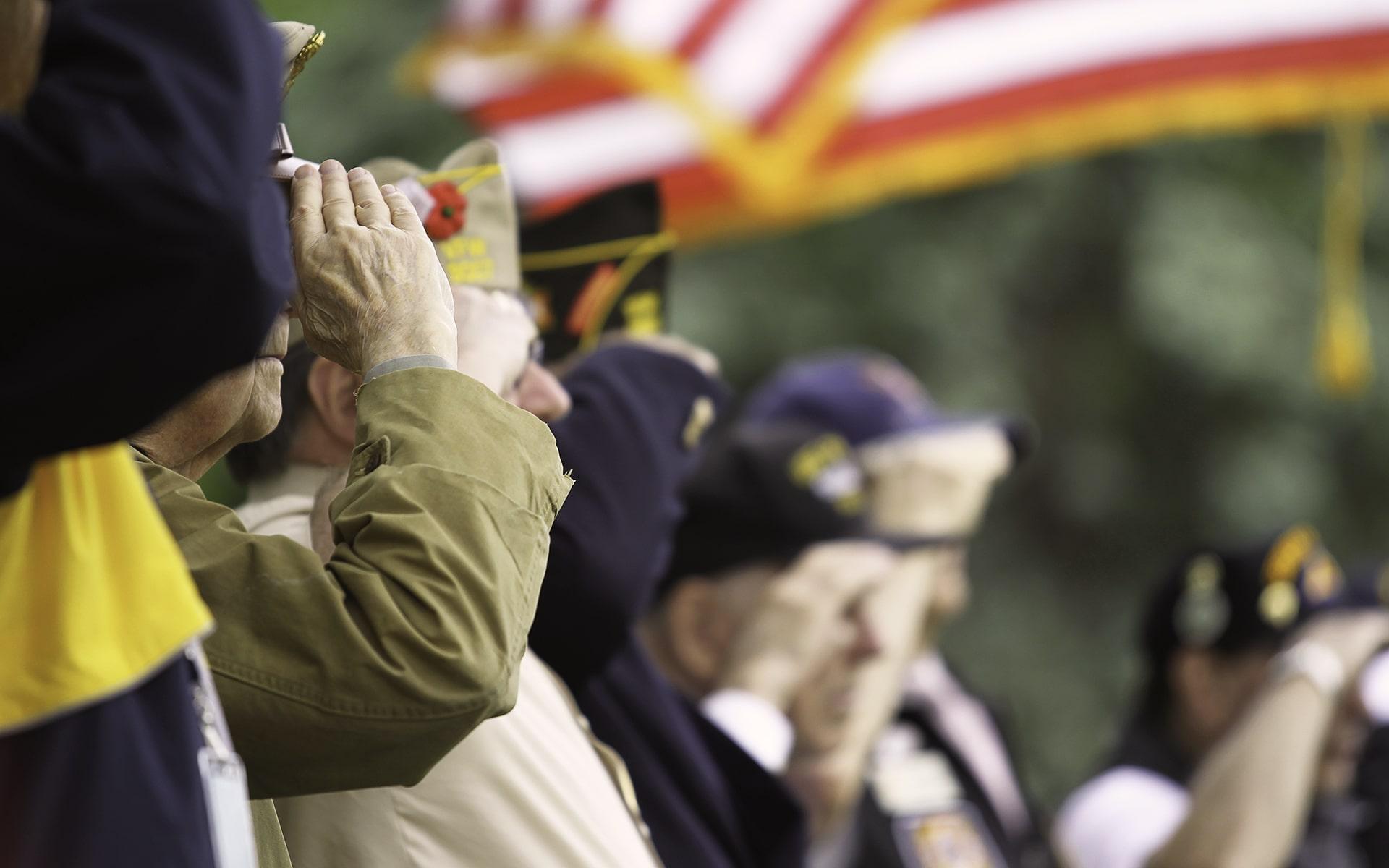 Senior veterans salute the American flag.