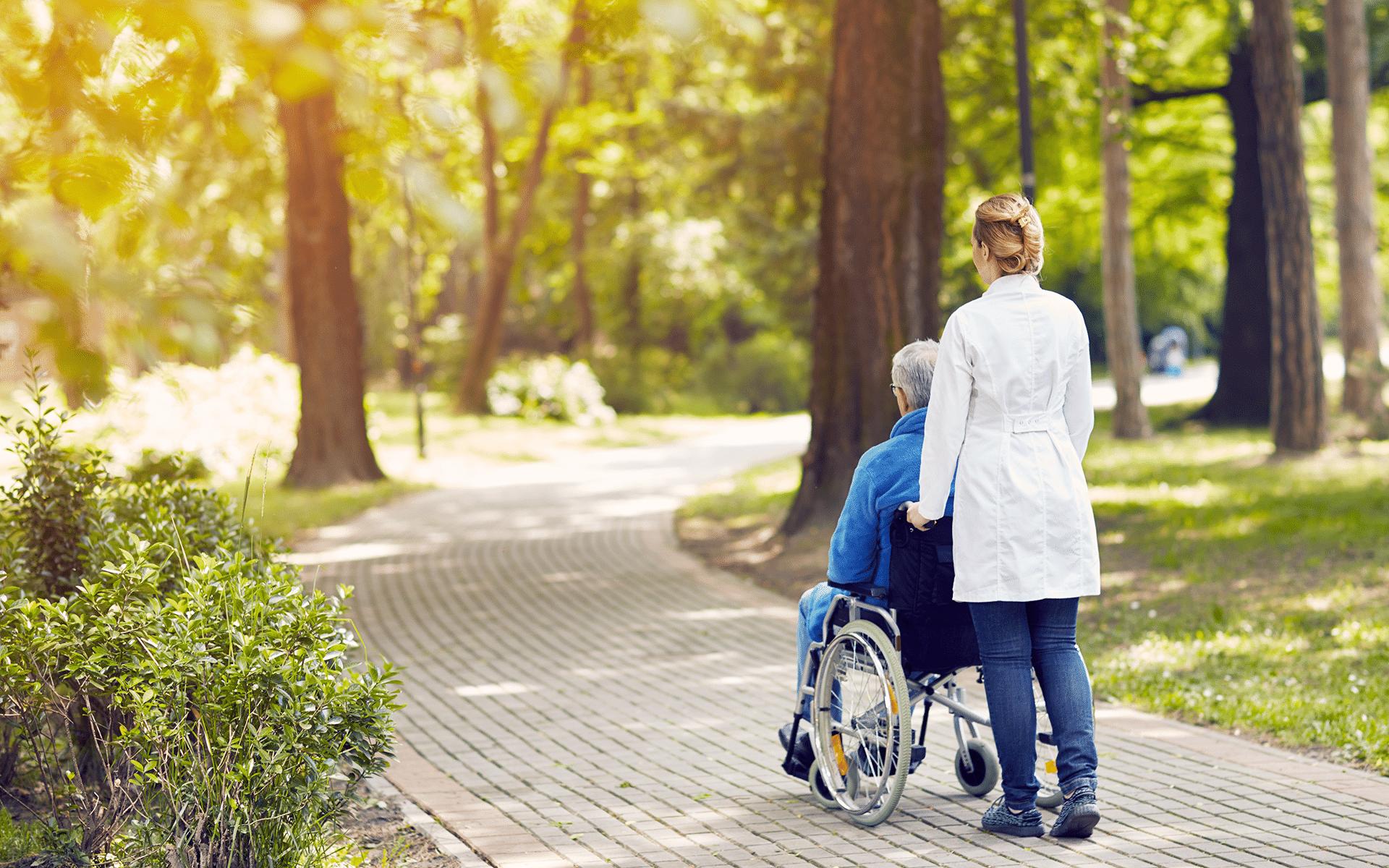 A hospice nurse taking an elderly man on a walk in his wheelchair.