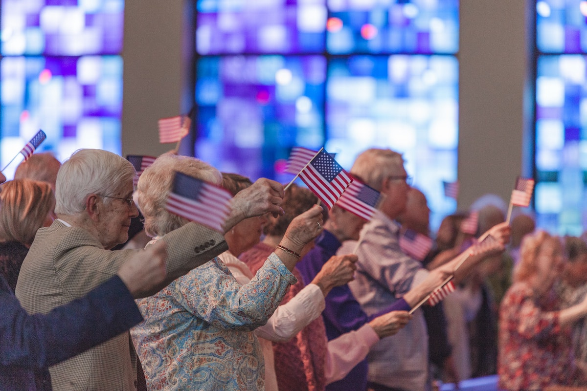 a group of seniors waves small flags