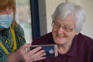 caregiver shows cell phone to the person they're providing care for