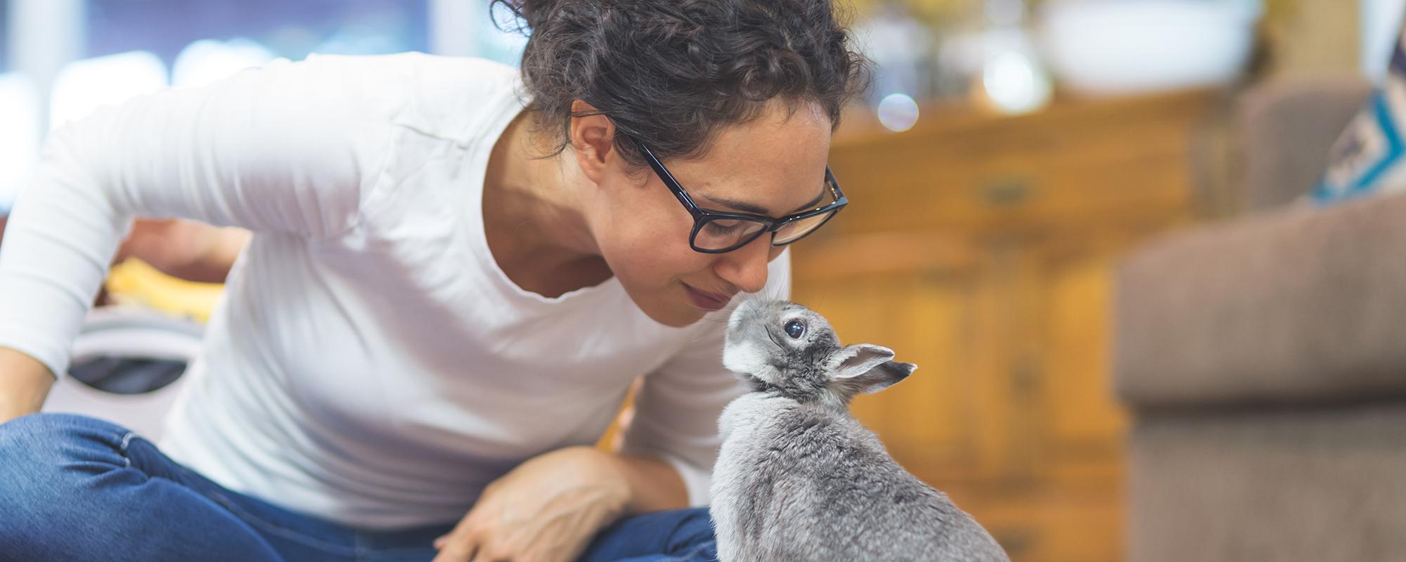 A woman admiring her pet bunny.
