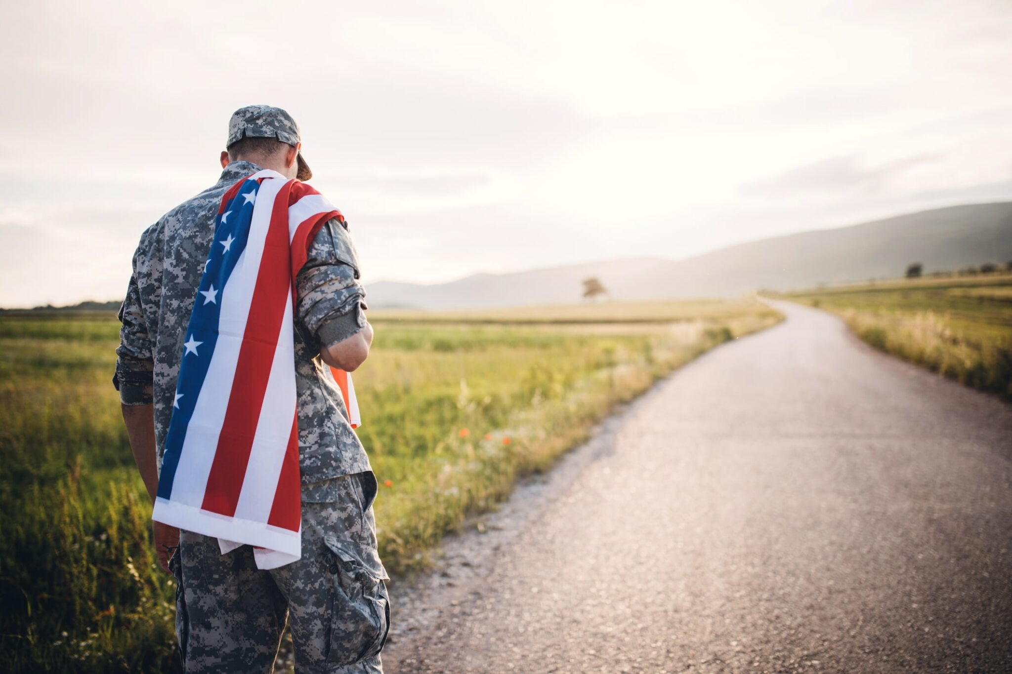 A solider walks down a road alone carrying the U.S Flag on his back.