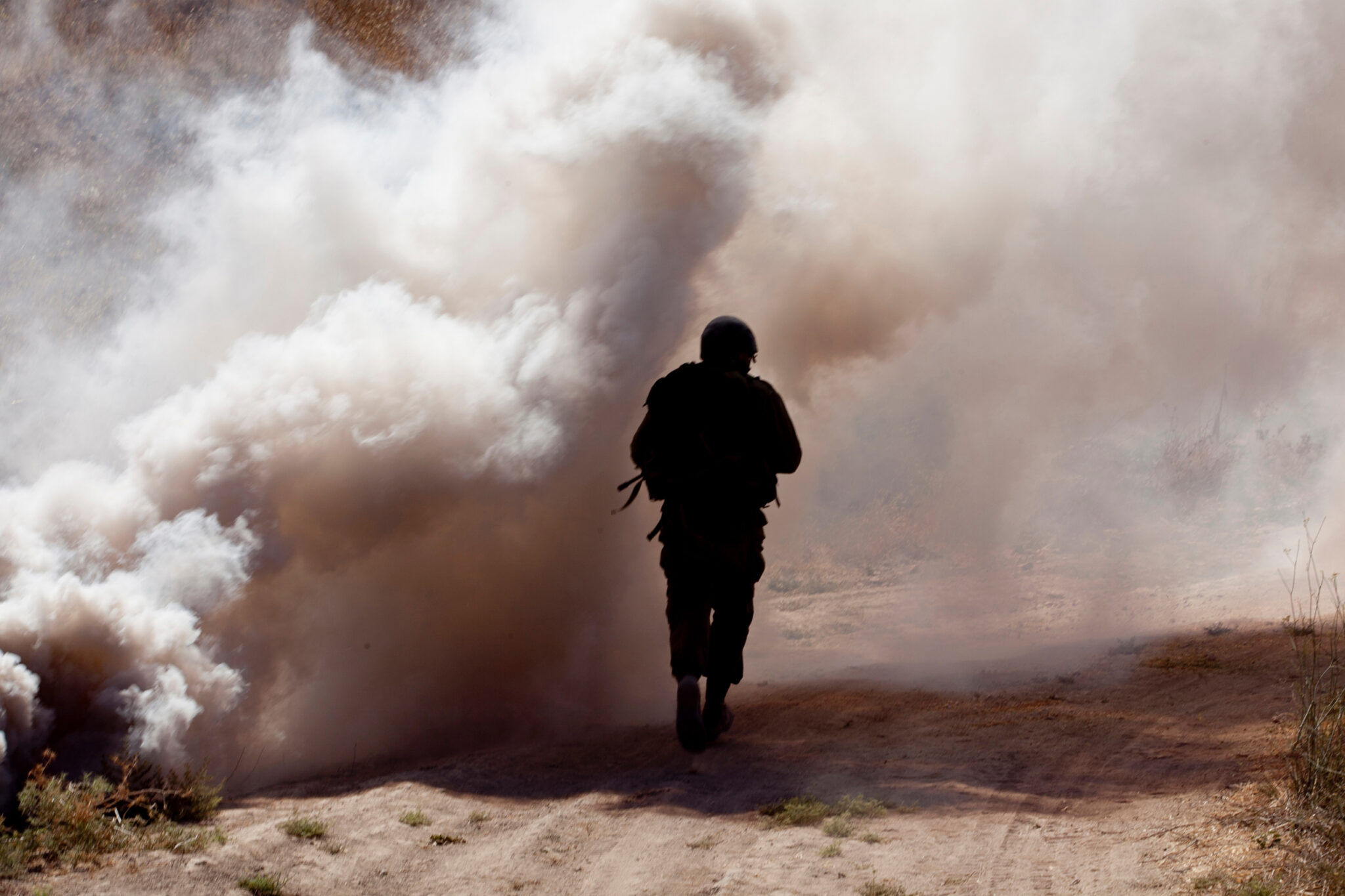 Rear View Of Soldier running through smoke and smog that may contain asbestos.