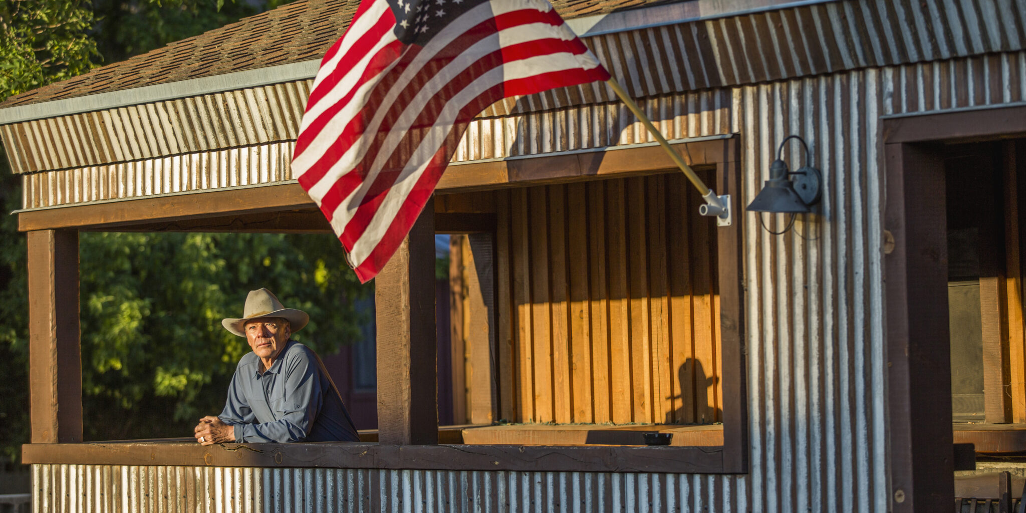 Mature cowboy on porch with American flag