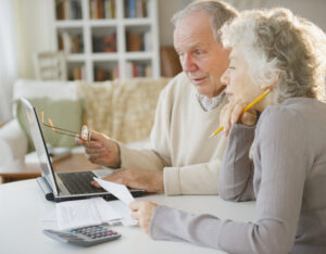 Elderly couple works on together on paperwork with a laptop in front of them