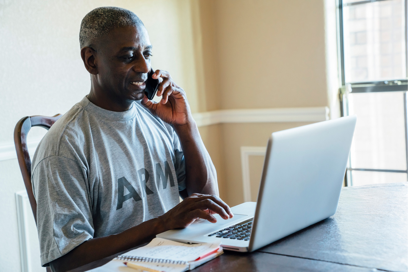 Army veteran on phone and laptop looking for online resources.