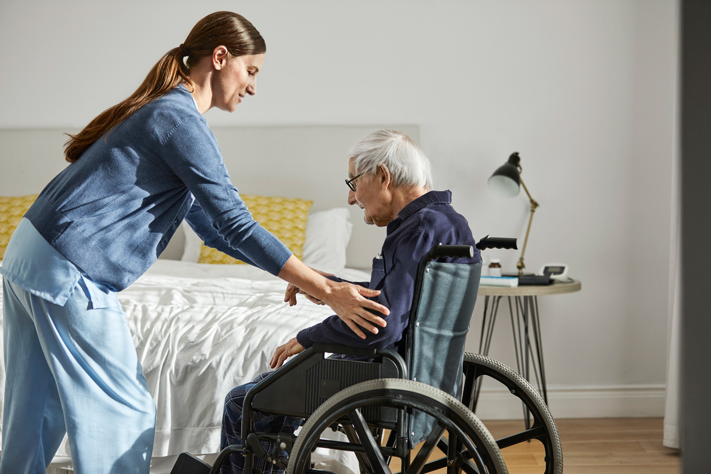 Young caregiver helping senior man in wheel chair.