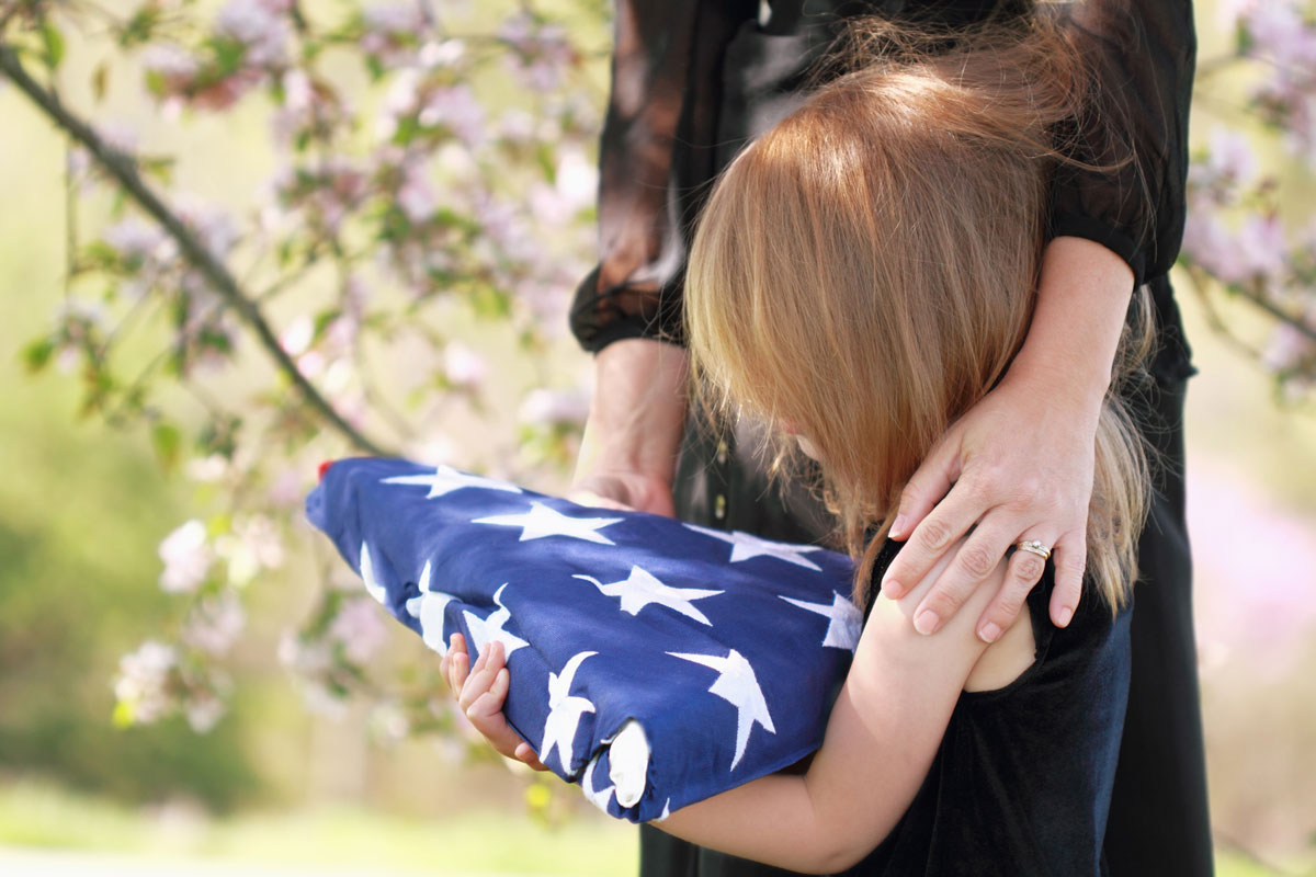 young girl with mother holding folded flag at veteran funeral
