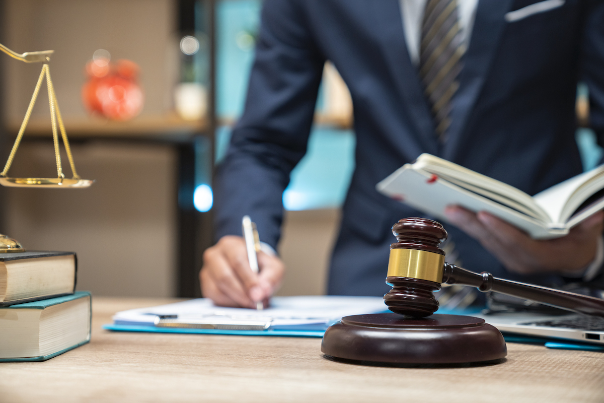 closeup of a lawyer in their office writing on paperwork with a gavel in front of them