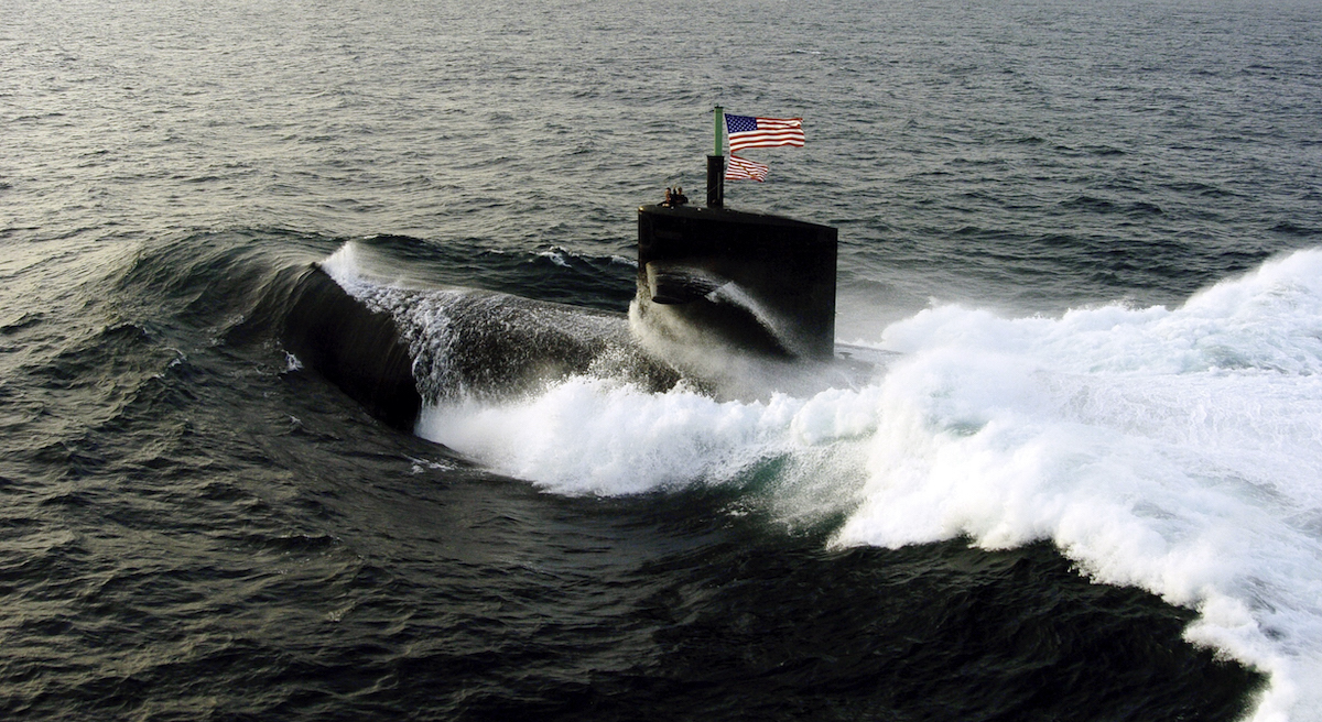 United States Navy submarine comes to the surface of the ocean with the American flag flying on top.
