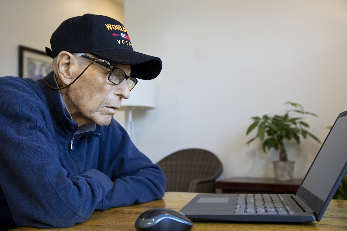 Veteran wearing VFW ball cap focuses on a laptop on the table in fronton him